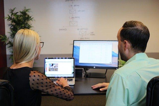 tvorba stránek není práce jen jednoho člověka, vždy se spolupracuje v týmu (žena s mužem diskutují nad počítači a prací)