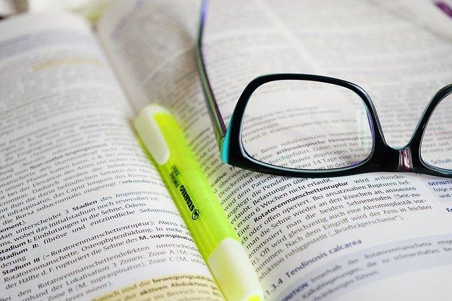 otevřená kniha, brýle, zvýrazňovač