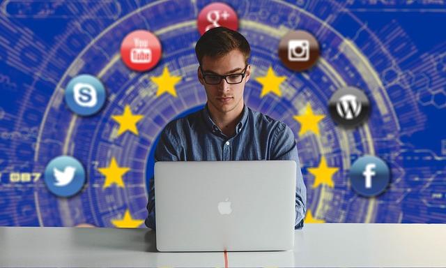 muž, který pracuje na počítači, v pozadí za sebou má znak EU a okolo znaky sociálních sítí atd.