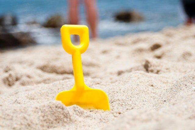 žlutá lopatka zapíchnutá v písku